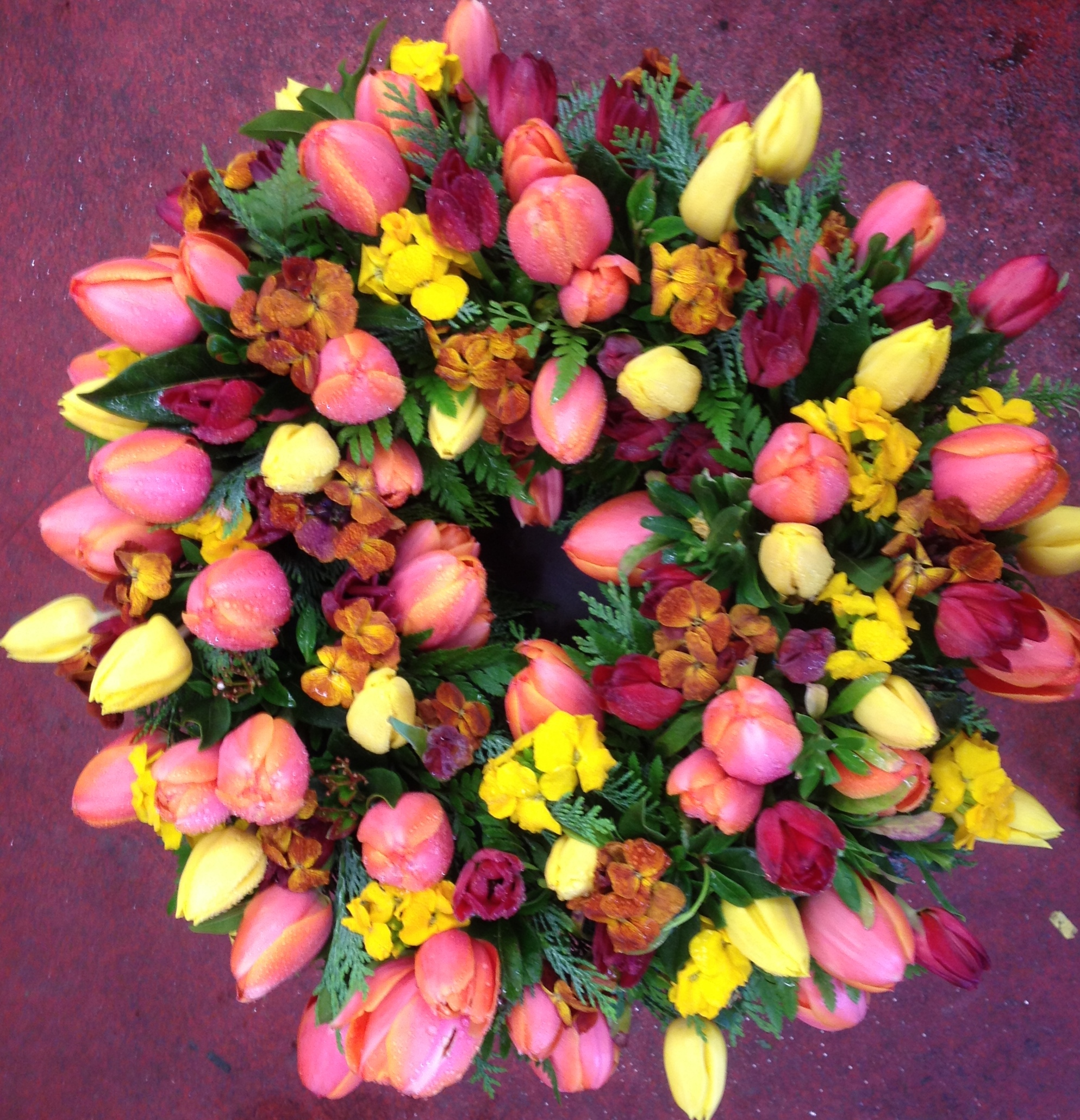 Funeral flower pictures john thomas florist vibrant wreath with tulips and wall flowers izmirmasajfo
