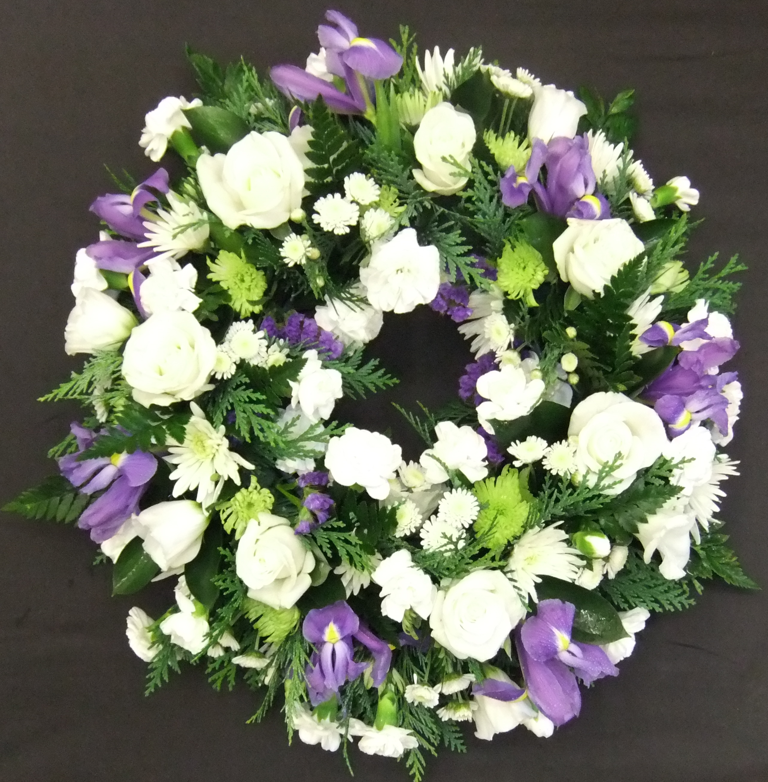 Flowers for funerals john thomas florist traditional wreath in white purple and green izmirmasajfo Choice Image